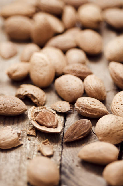 Close-up of whole and cracked Almonds with rustic on wooden table — Stock Photo