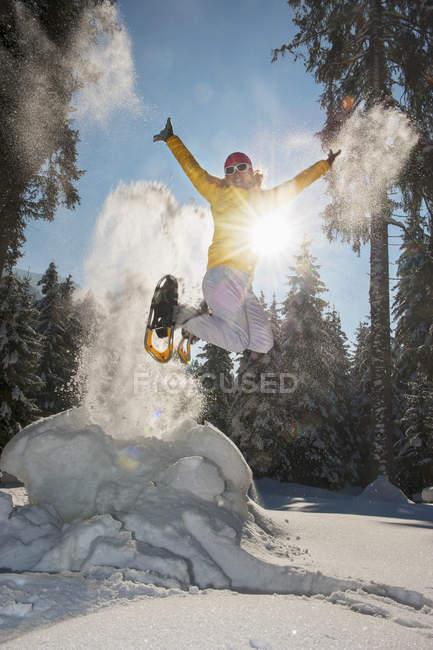 Femme avec des raquettes en sautant dans le paysage d'hiver d'Altenmarkt-Zauchensee, Autriche — Photo de stock