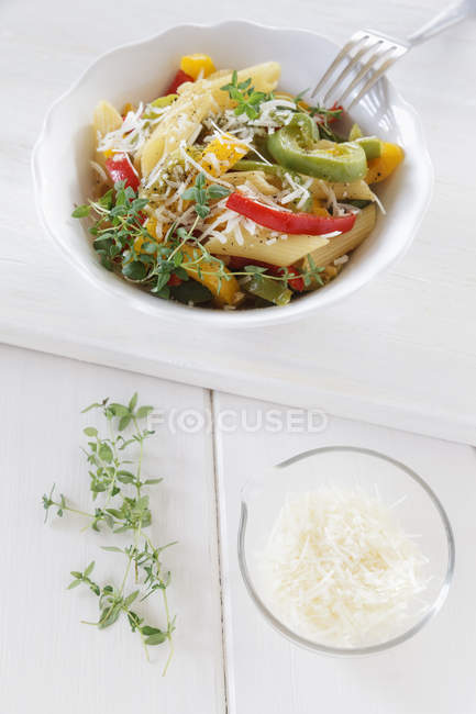 Чаша перец макароны с сыром пармезан и тимьяном на деревянном столе, крупным планом — стоковое фото