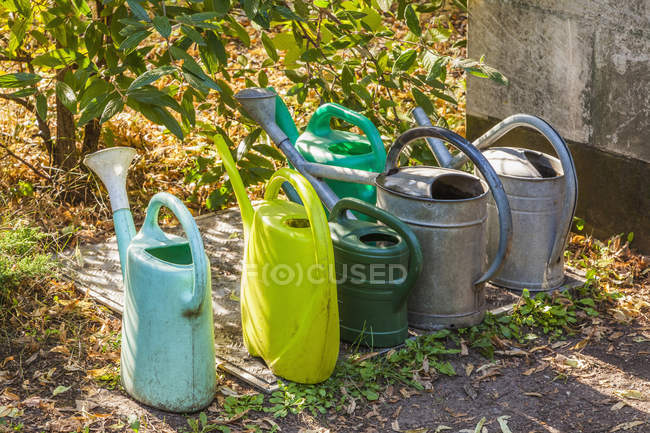 Variation of watering cans over ground — Stock Photo