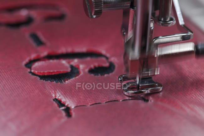 Вышивка с черным номером на красной ткани — стоковое фото