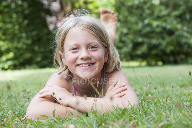 Smiling girl lying in grass and looking at camera — Stock Photo