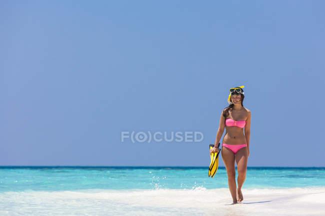 Maldivas, mujer joven caminando en la playa - foto de stock