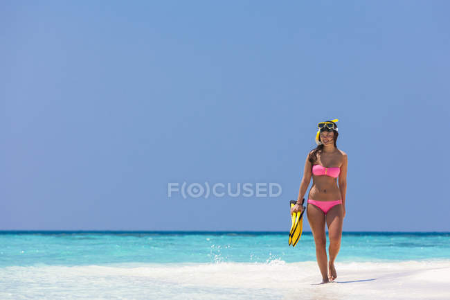 Maldives,Young woman walking on beach — Stock Photo