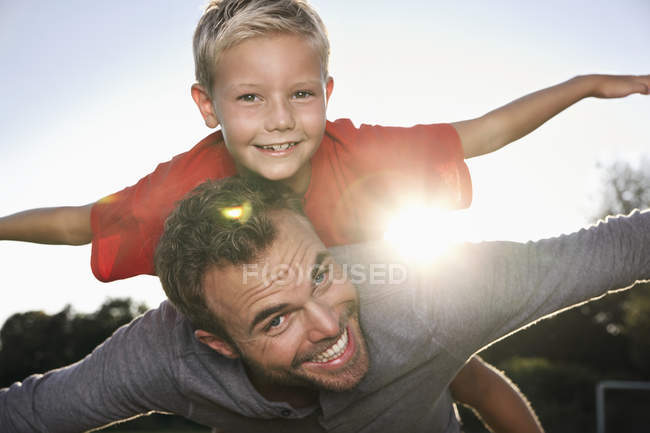 Father carrying son, pretending to fly — Stock Photo