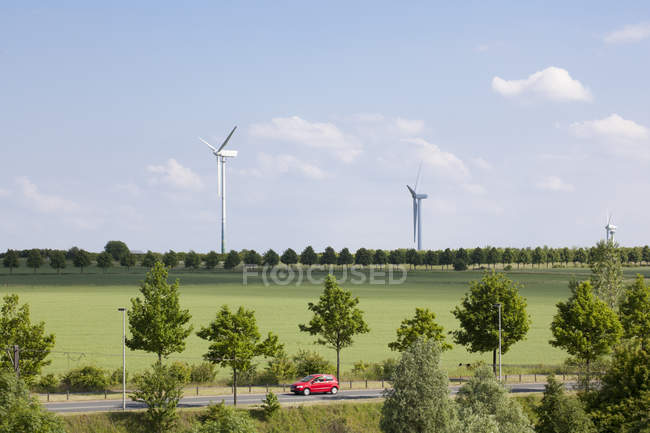 Germany, Hanover, wind turbines by green field, red car on road in foreground — Stock Photo