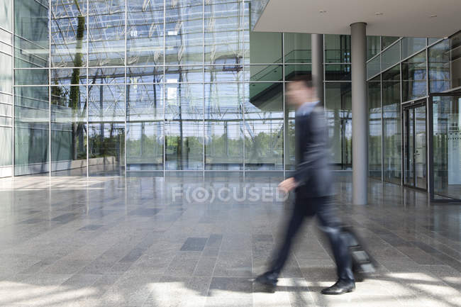 Businessman on the go pulling suitcase — Stock Photo