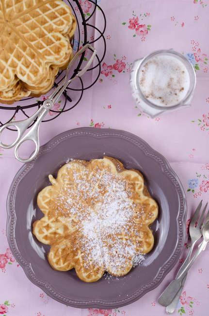 Вид сверху-в форме сердца вафли с пудрой сахара на плите с столовые приборы — стоковое фото