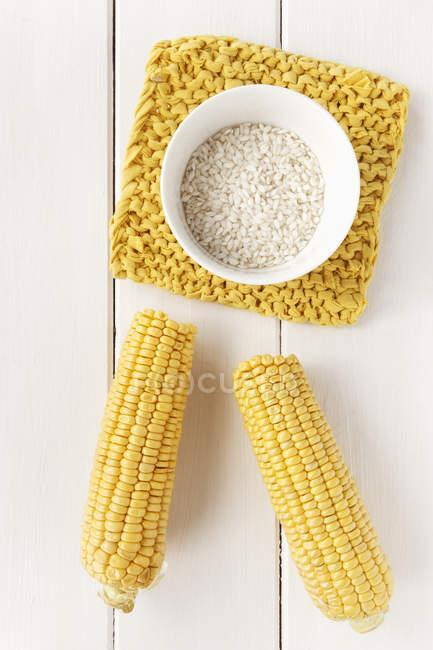 Початки кукуруза и рис арборио на белый деревянный стол, студия выстрел — стоковое фото