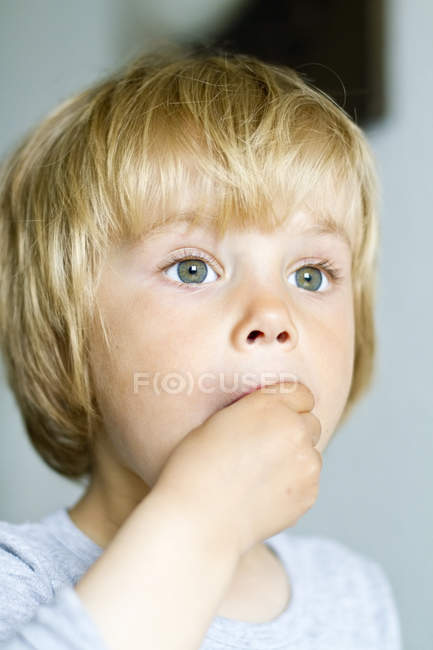 Girl looking sideways with hand in mouth — Stock Photo