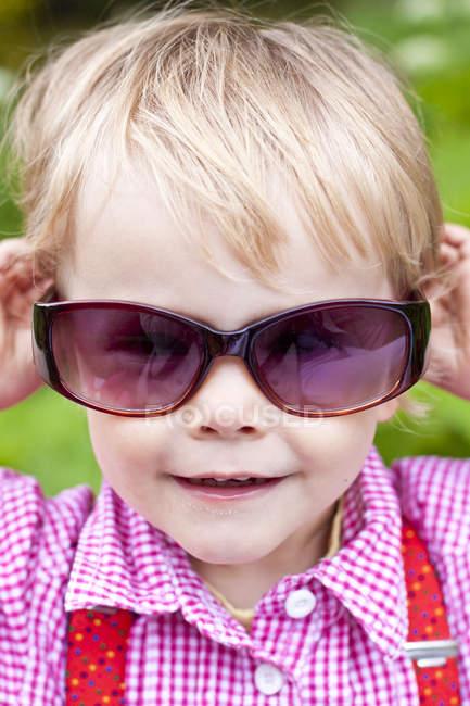 Blond little girl wearing sunglasses — Stock Photo