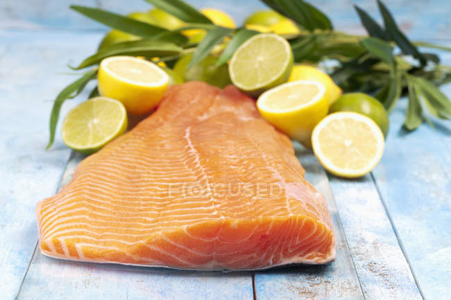Salmon fillet and citrus fruits on blue wooden table — Stock Photo