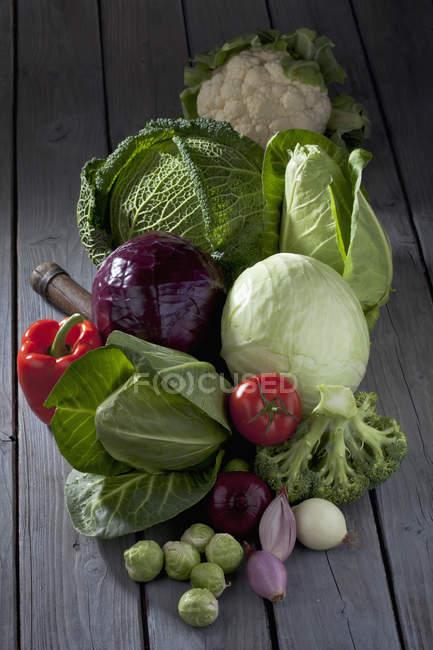Сорта капусты и овощи на сером деревянном столе — стоковое фото