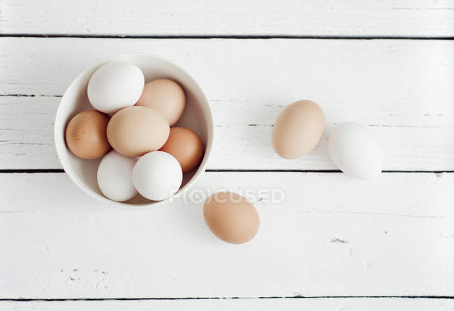 White and brown Eggs in bowl on white wooden table — Stock Photo