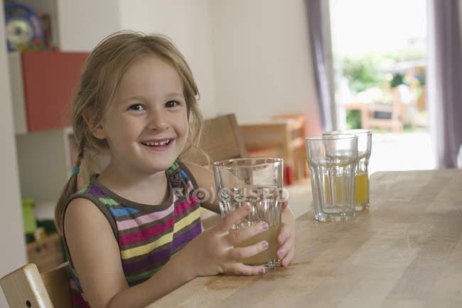 Niña sonriente sentada en la cocina con un vaso de agua - foto de stock