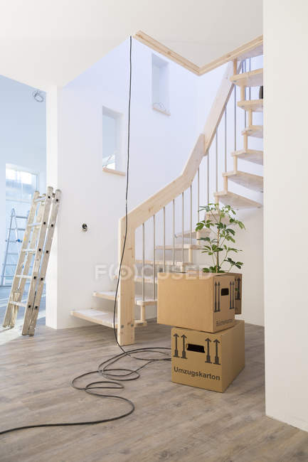 Staircase and cardboard boxes in new home — Stock Photo