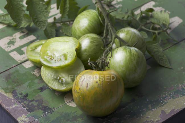 Половинки и весь зеленый Зебра помидоры на зеленое дерево — стоковое фото