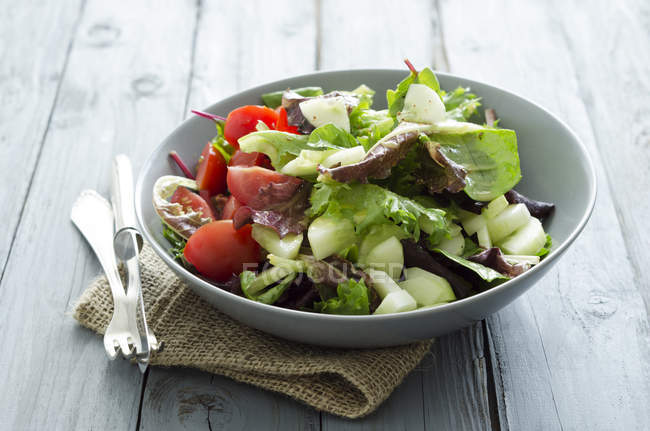 Mixed salad with tomatoes with vinegar and oil dressing in bowl on sackcloth — Stock Photo