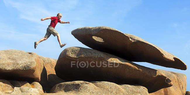France, Bretagne, Tregastel, Man jumping on rocks — Stock Photo