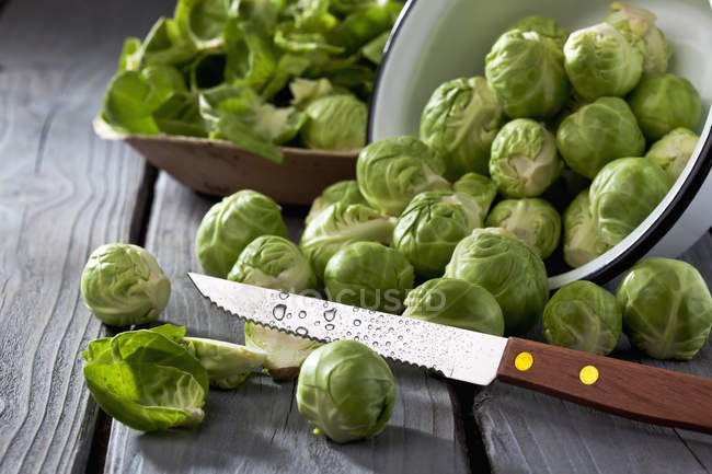 Upturned Bowl of brussels sprouts and knife on grey wooden table — Stock Photo