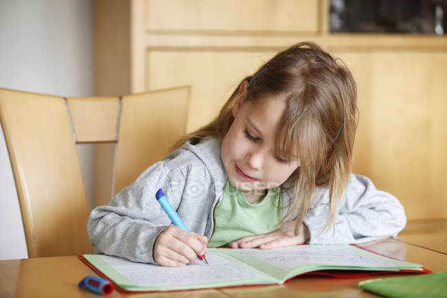 Concentré de fille à faire leurs devoirs au comptoir — Photo de stock