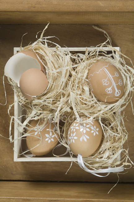 Painted eggs with eggshell in box on wooden surface — Stock Photo