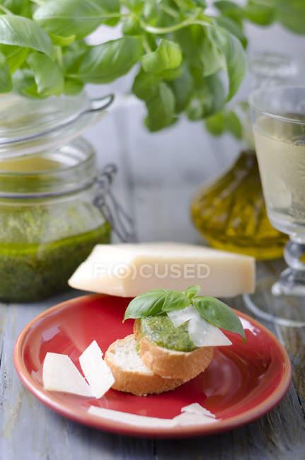 Pesto de albahaca fresca en rebanada de pan baguette servido en plato de arcilla roja con queso, tarro de pesto y hojas de albahaca fresca sobre fondo - foto de stock