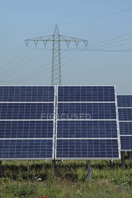 Alemanha, Baviera, Painéis solares com pólo de energia em segundo plano — Fotografia de Stock