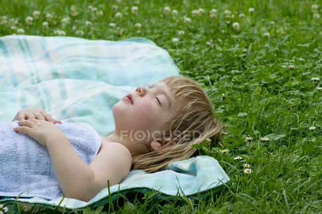 Girl sleeping on picnic blanket in meadow — Stock Photo