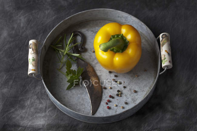 Желтый перец с ножом, перца и травы на металлические подносы — стоковое фото