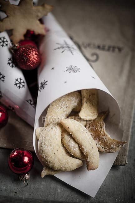 Biscoitos de amêndoa em saco de papel com bugigangas vermelhas de Natal na mesa de madeira — Fotografia de Stock