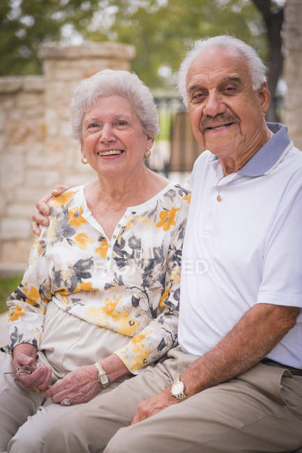 Portrait of senior couple sitting outdors — Stock Photo