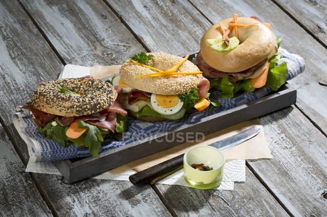 Три различных бубликов, украшенный с салями, колбаса, ломтики бекона, рукколы, салата, огурец морковь, яйцо, сливочный сыр и кресс-салат и петрушки — стоковое фото
