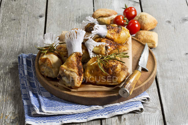Chicken drums on wooden chopping board — Stock Photo