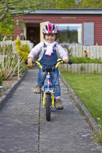 Bicicleta de chica a caballo en el patio trasero - foto de stock