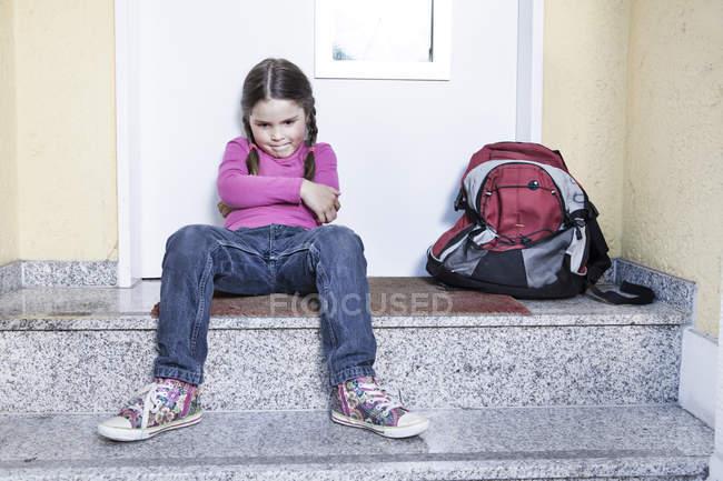 Menina esperando na escola sentado nas escadas com mochila — Fotografia de Stock