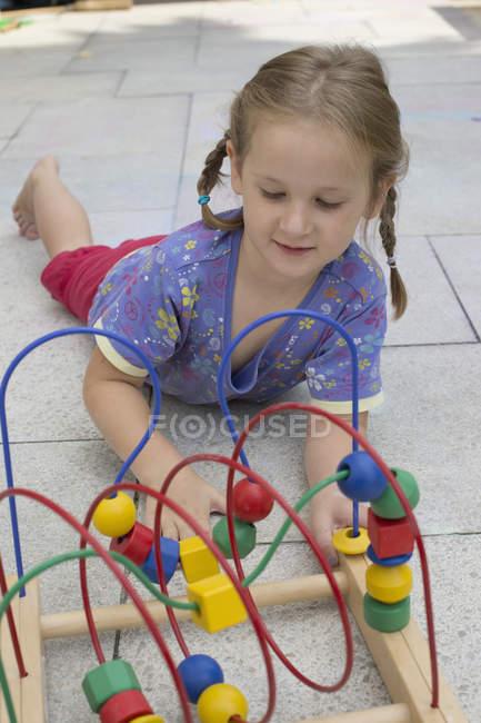 Niña jugando con colorido juguete de madera - foto de stock