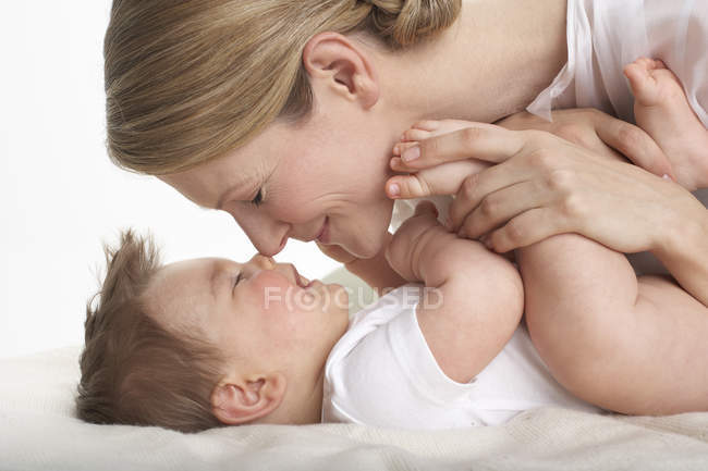 Mother and her baby boy kissing nose-to-nose — Stock Photo