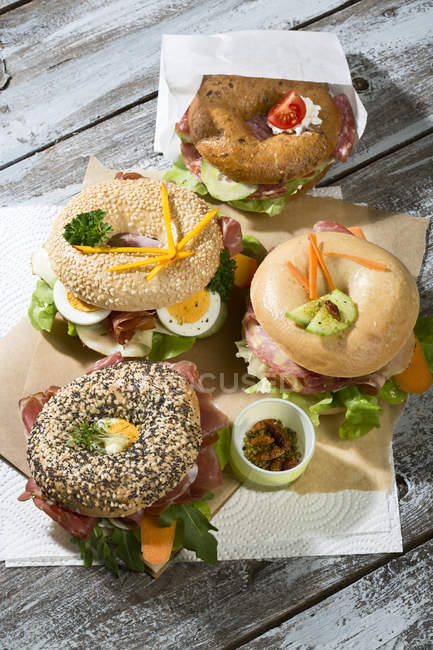 Vier verschiedene Bagel mit Salami, Wurst, Scheiben von Speck, Rucola, Tomaten, Salat, Gurke, Karotte, Ei, Frischkäse und Kresse und Petersilie garniert — Stockfoto