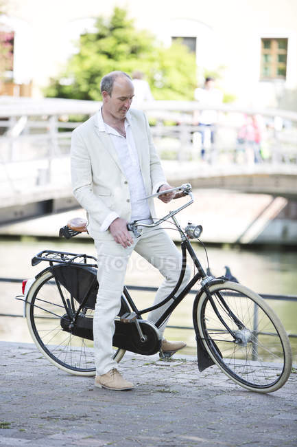 Mature man with bicycle and using digital tablet, smiling — Stock Photo