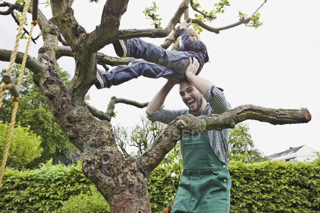 Pai ajudando filho a subir árvore, sorrindo — Fotografia de Stock