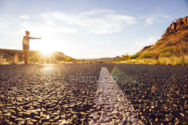 Низький кут зору молода жінка автостопом на дорозі — стокове фото