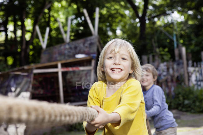 Boys in playground smiling tug-of-war — Stock Photo