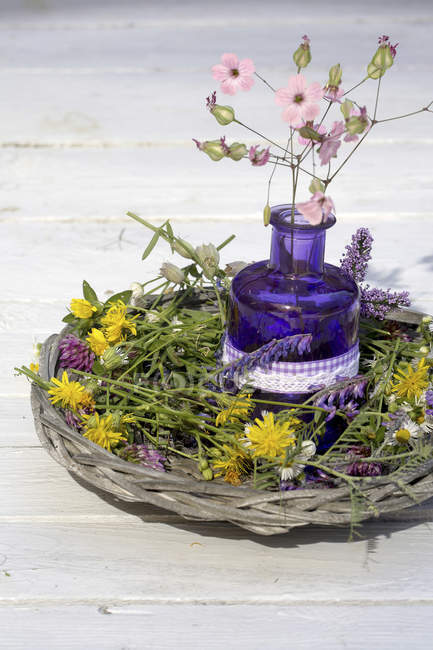 Basket with colourful wildflowers and purple glass — Stock Photo