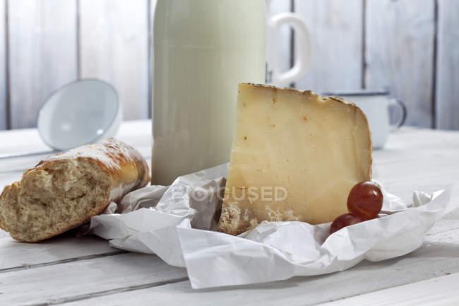 Queijo de ovelha com leite e pão na mesa de madeira com papel — Fotografia de Stock