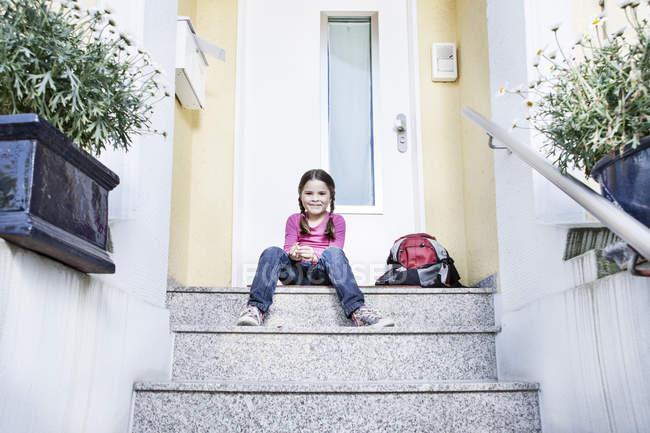 Menina esperando na escola sentado nas escadas com mochila, sorrindo — Fotografia de Stock