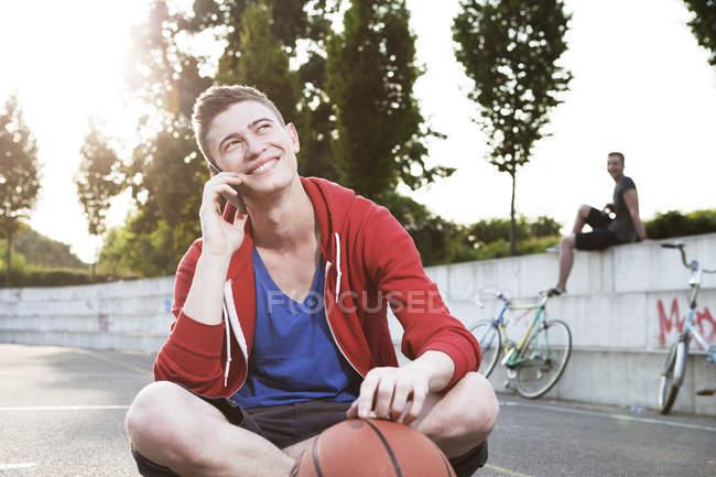 Jovem com smartphone e basquete — Fotografia de Stock