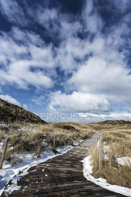 Germany, boardwalk on coast with snow at Spiekeroog — Stock Photo