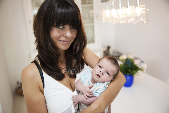 Smiling young mother carrying her newborn son in her arms — Stock Photo