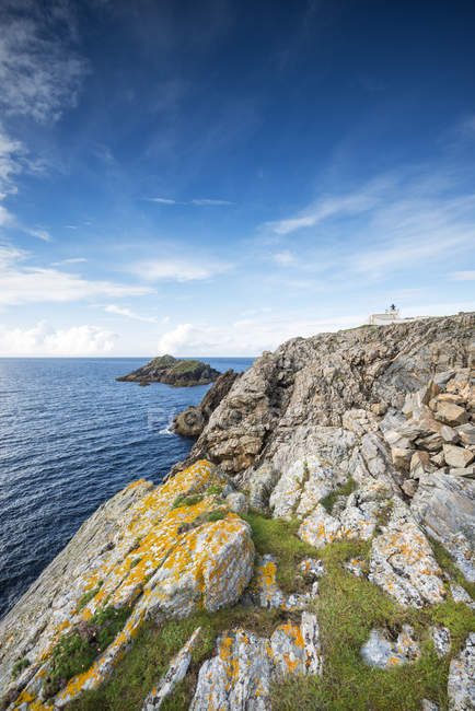 Reino Unido, Escocia, Sutherland, Rugged coastal landscape with the Strathy Point Lighthouse in front of the North Sea - foto de stock